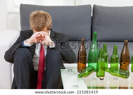 Depressed businessman drunk at home with empty bottles on table - stock photo