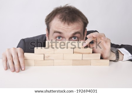 Depressed businessman hides behind the wall  - stock photo