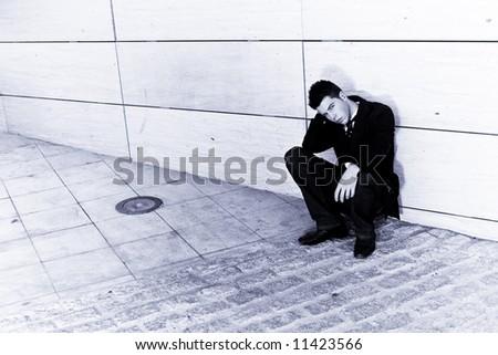 Depressed businessman in urban background, blue toned. - stock photo