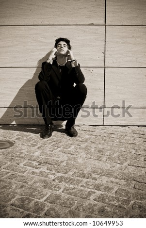 Depressed businessman in urban background, sepia toned.