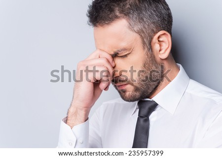 Depressed businessman. Portrait of frustrated mature man in shirt and tie touching his nose and keeping eyes closed while standing against grey backgroundWorried businessman.  - stock photo