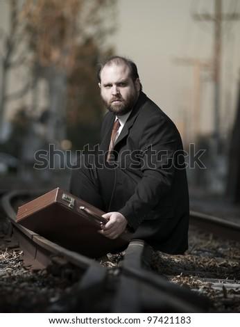Depressed businessman sitting on railroad tracks - stock photo