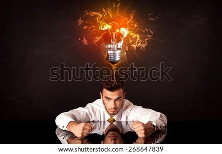 Depressed businessman sitting under a blowing idea bulb - stock photo