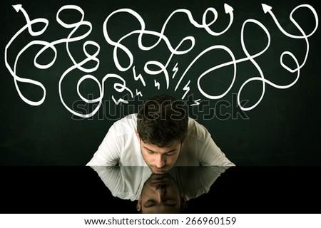 Depressed businessman sitting under white drawn direction lines - stock photo