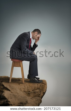depressed businessman suffering depression on a cliff ledge stress concept