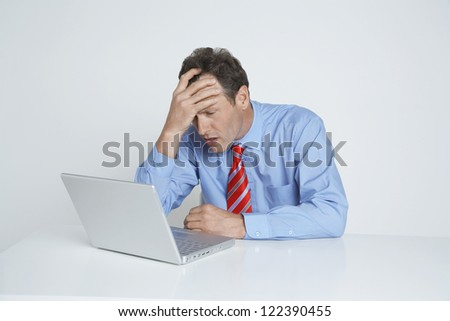 Depressed businessman with hand on head sitting with laptop