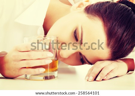Depressed businesswoman in depression drinking alcohol. - stock photo