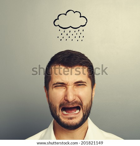 depressed crying man with drawing storm cloud over grey background - stock photo
