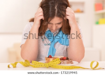 Depressed dieting woman with cake and measuring tape - stock photo