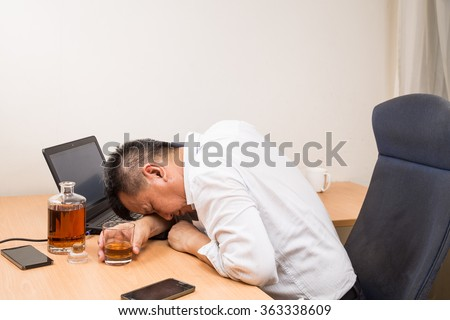 Depressed, frustrated and stressful Asian business manager drunk in office