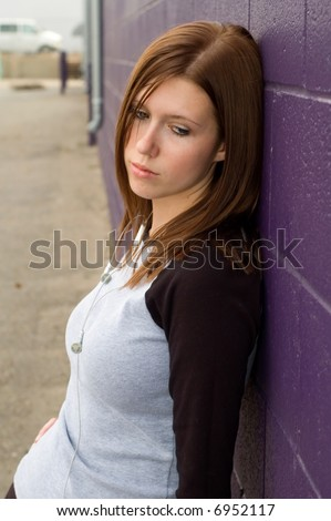 Depressed girl leaning against a brick wall. - stock photo