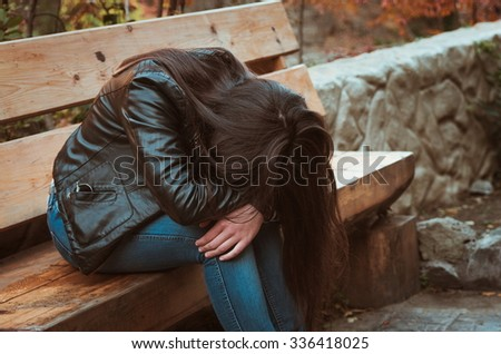 depressed girl sitting on bench in the park - stock photo