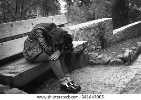 depressed girl sitting on bench in the park