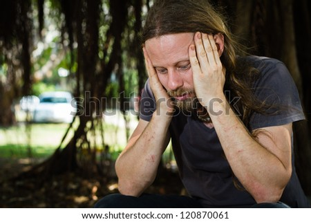 Depressed homeless man thinking outdoors - stock photo
