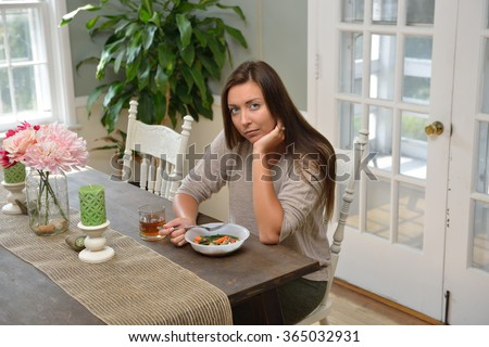 Depressed looking young woman eating a frozen dinner alone at her dining room table - stock photo
