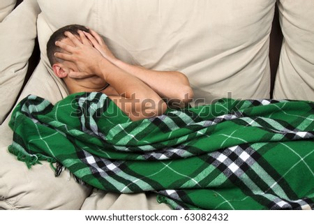 Depressed male crying, lying on the sofa cover face by hands - stock photo