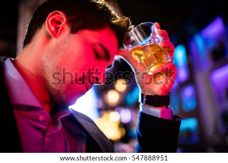 Depressed man having whisky drink at bar counter in bar
