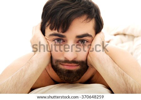 Depressed man in bedroom. - stock photo