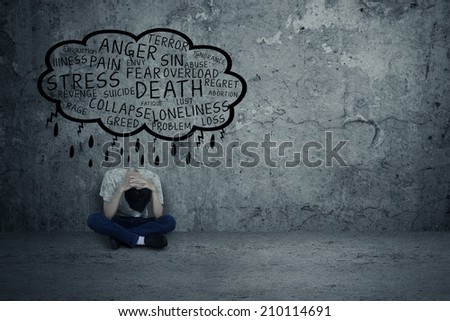 Depressed man sitting alone because many problems - stock photo
