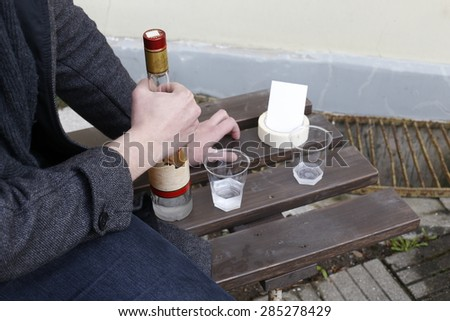 depressed man sitting and drinking on a bench with a bottle - stock photo