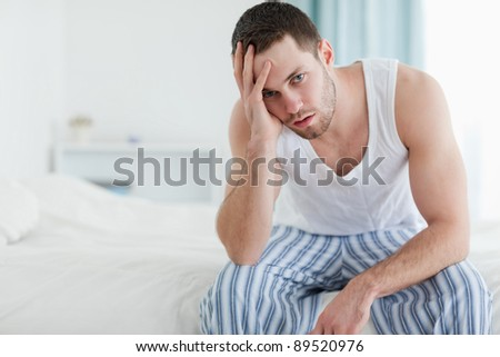 Depressed man sitting on his bed while looking at the camera - stock photo