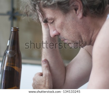Depressed man with alcohol bottle - stock photo