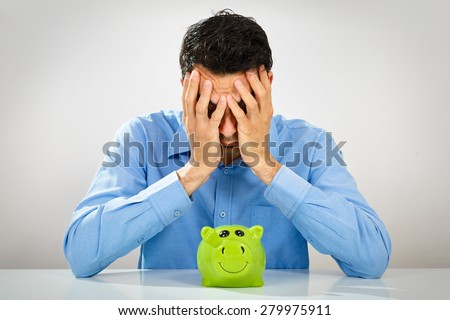 Depressed man with piggy bank - stock photo