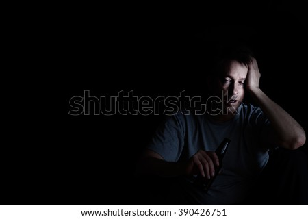 Depressed mature man drinking in dark. Selective focus on face with light. Depression concept.