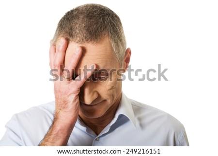 Depressed mature man touching his head. - stock photo