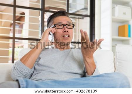 depressed matured asian man on the phone - stock photo