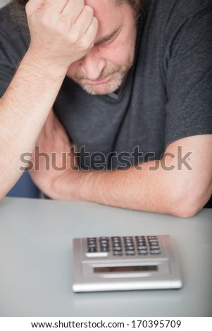 Depressed middle-aged man doing his finances holding his head in his hand as he stares at the calculator - stock photo