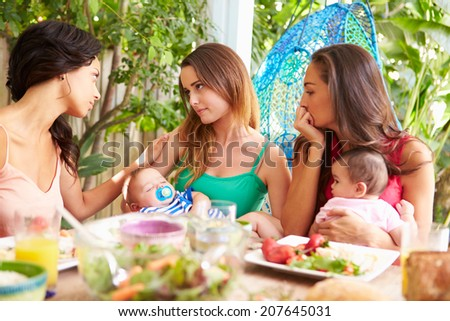 Depressed Mother With Baby Talking To Friends - stock photo