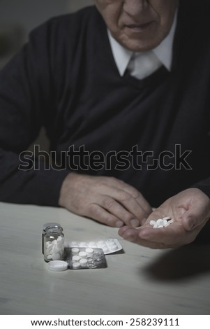 Depressed old man taking a handful of hypnotics - stock photo