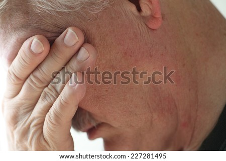 Depressed older man averts his head, covering his eyes with a hand. - stock photo