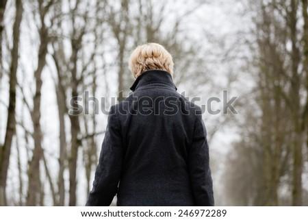 Depressed or sad woman walking down a barren path in winter - stock photo