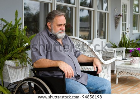 Depressed paraplegic man sits in his wheelchair on the patio. - stock photo