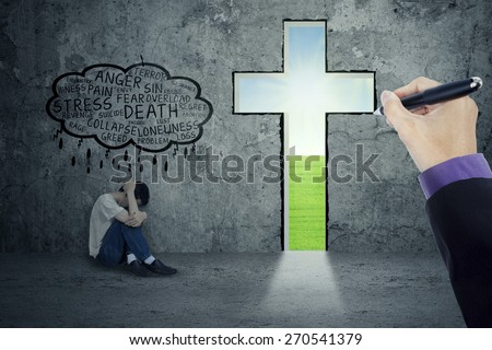Depressed person thinking his problem with a hand drawing a cross in a wall - stock photo