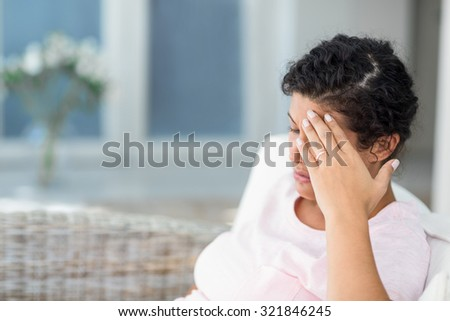 Depressed pregnant woman sitting on sofa at home