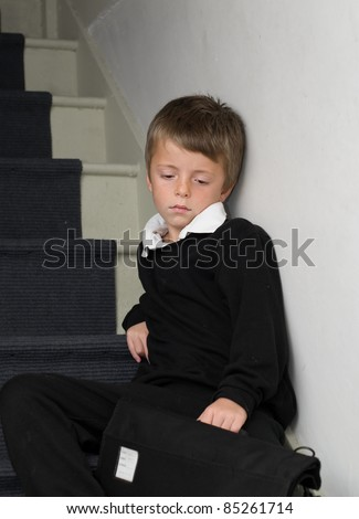 Depressed Primary School child sitting on the stairs. - stock photo
