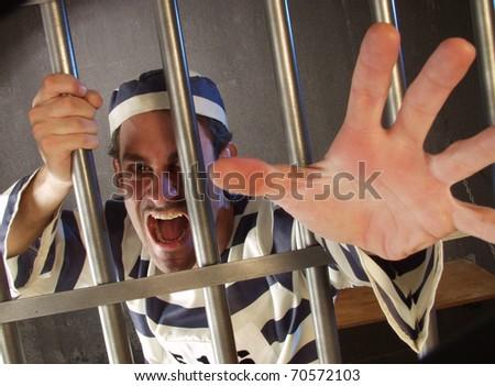 Depressed prisoner in a prison cell. - stock photo
