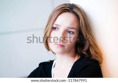 Depressed, sad woman in the living room - stock photo