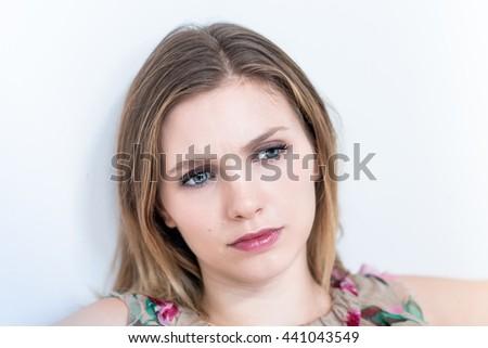 Depressed, sad woman on white background - stock photo
