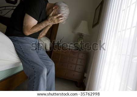 Depressed senior man in bedroom setting with natural light. - stock photo