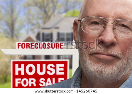 Depressed Senior Man in Front of Foreclosure Real Estate Sign and House. - stock photo