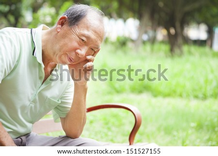 depressed senior man sitting in the park - stock photo