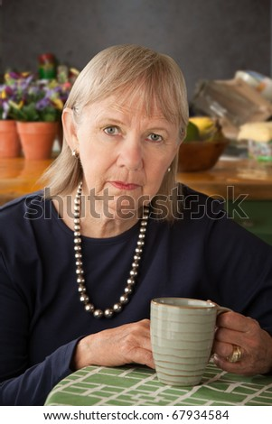 Depressed senior woman at home with coffee or tea - stock photo