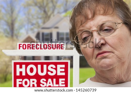 Depressed Senior Woman in Front of Foreclosure Real Estate Sign and House. - stock photo