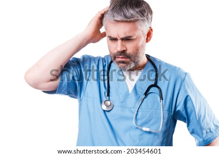 Depressed surgeon. Side view of depressed mature doctor touching his face with hand and keeping eyes closed while standing isolated on white - stock photo