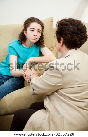 Depressed teen girl gets counseling and comfort from a caring therapist. - stock photo