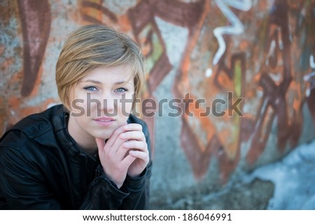 Depressed teen girl in leather jacket, with graffiti wall as background - stock photo
